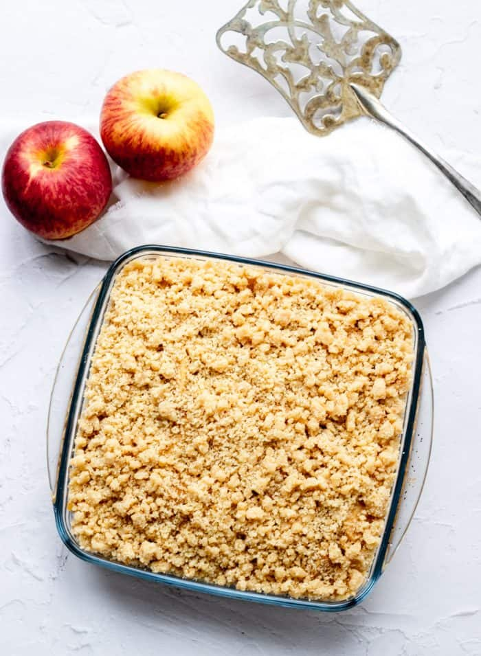 glass dish of apple crumble with apples, cloth and serving spatula on grey background