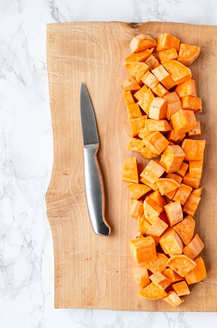 diced sweet potato on a wooden cutting board
