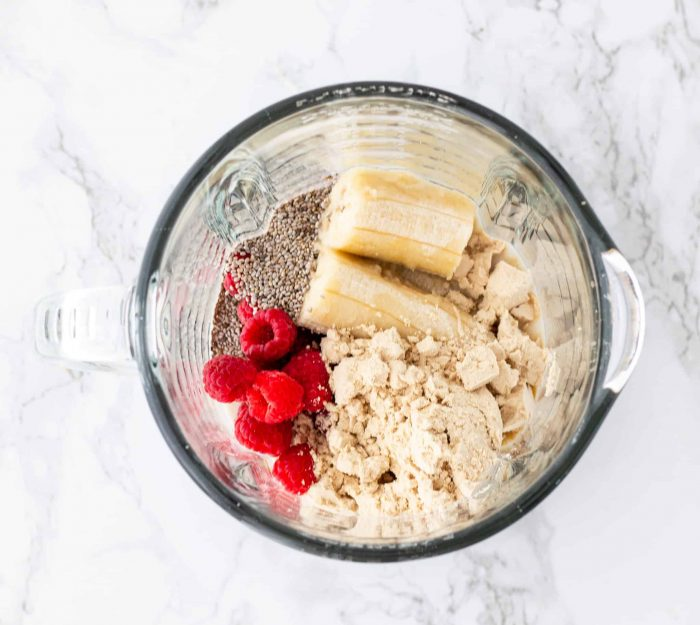 ingredients in blender for raspberry banana smoothie