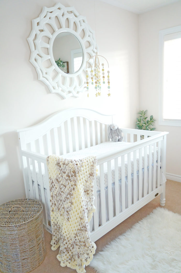 A beautiful white crib in a gender neutral baby nursery