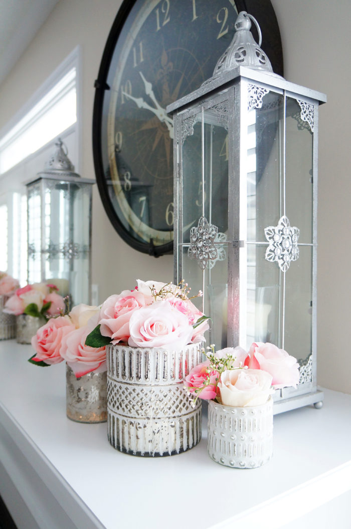 Pink Spring rose bouquets in silver votives with candles on fireplace mantel