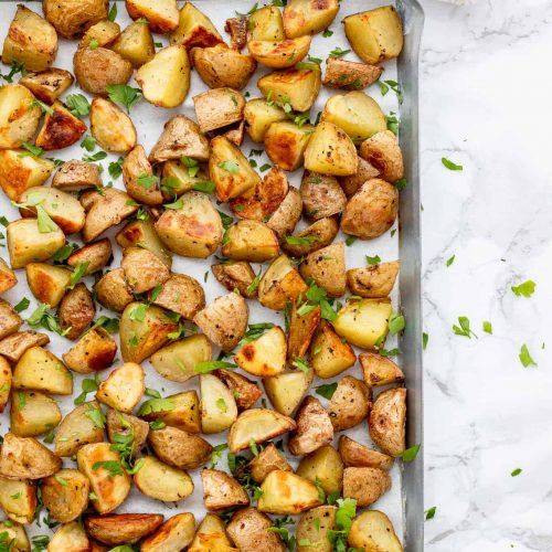 roasted potatoes on a baking sheet with fresh parsley