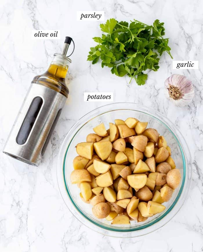 ingredients for roasted garlic potatoes with labels on marble background