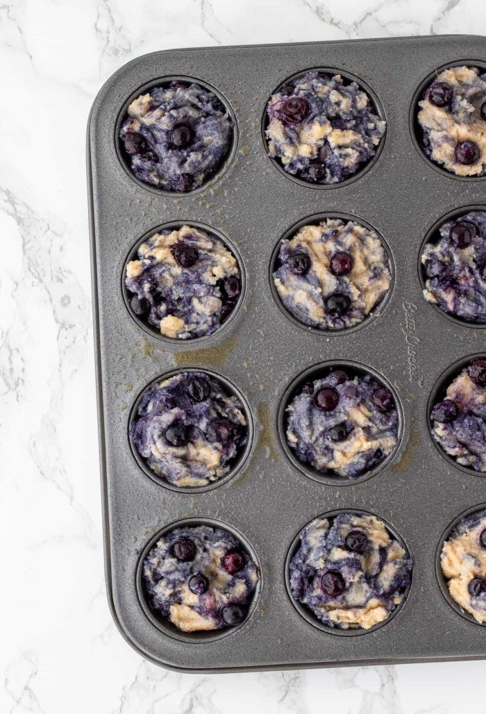 Uncooked blueberry muffins in mini muffin tin