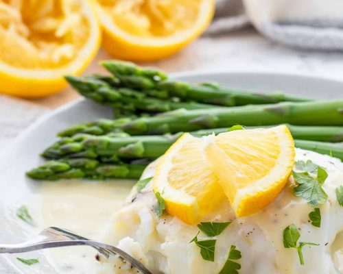 Using fork to eat fish with lemon sauce and asparagus