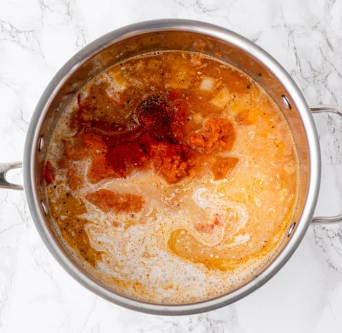 coconut milk, spices, pumpkin and red curry paste cooking in a large sauce pan on marble background