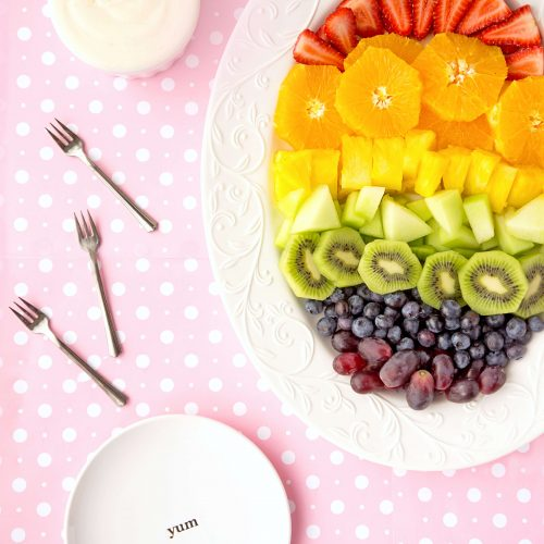 Rainbow Fruit on an oval tray served with Honey Greek Yogurt Dip on pink polka dot background