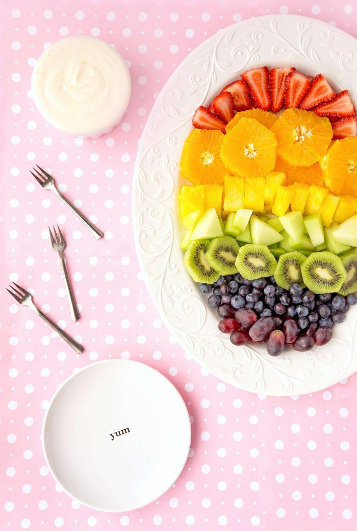Rainbow Fruit on an oval tray served with Honey Greek Yogurt Dip on pink polka dot background