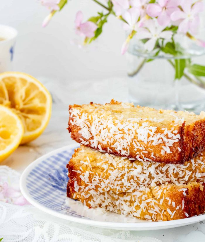Pieces of lemon coconut loaf stacked on a plate