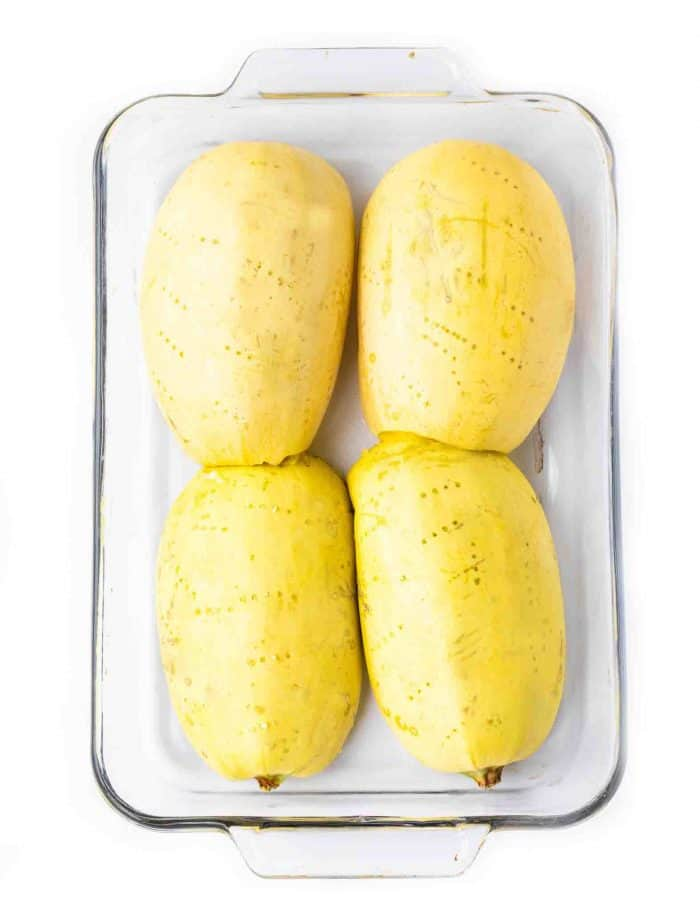 Four spaghetti squash halves face down in a large glass baking dish on a white background