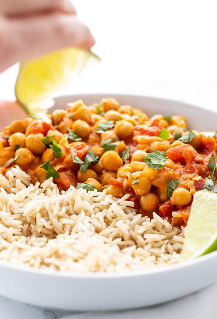 squeezing lime juice over chickpea curry