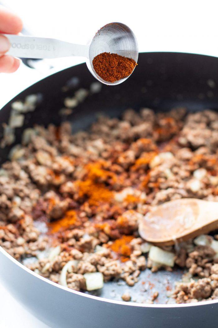 Adding taco seasoning to pan of beef