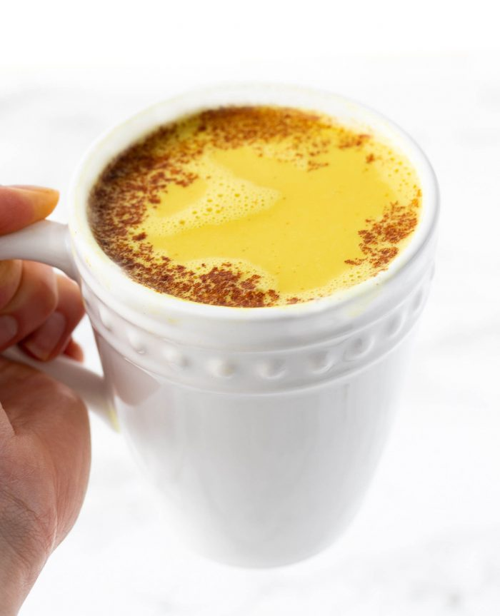 holding a cup of golden milk latte