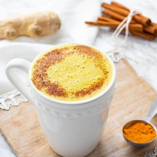 turmeric latte with spoonful of turmeric, cinnamon stick and ginger