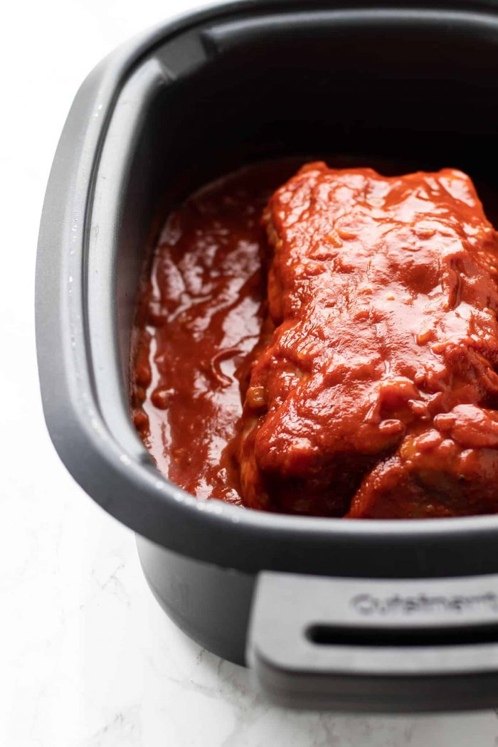 pork shoulder in a crock pot with BBQ sauce