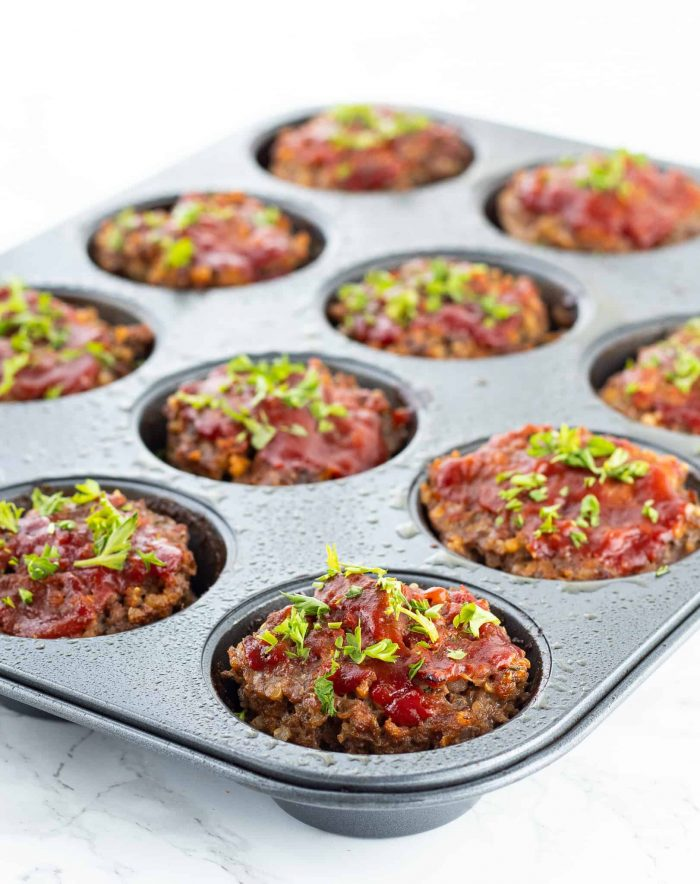 The baked mini meatloafs in the muffin tin garnished with fresh herbs