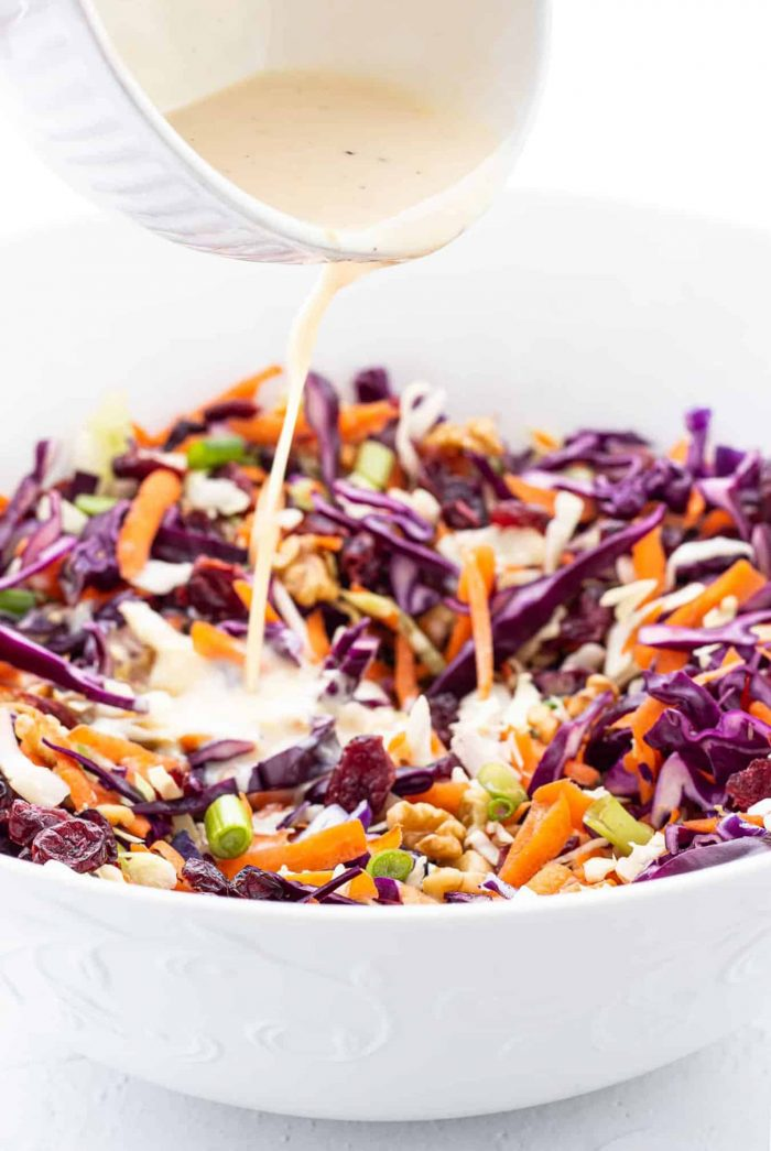 pouring creamy dressing into bowl of coleslaw