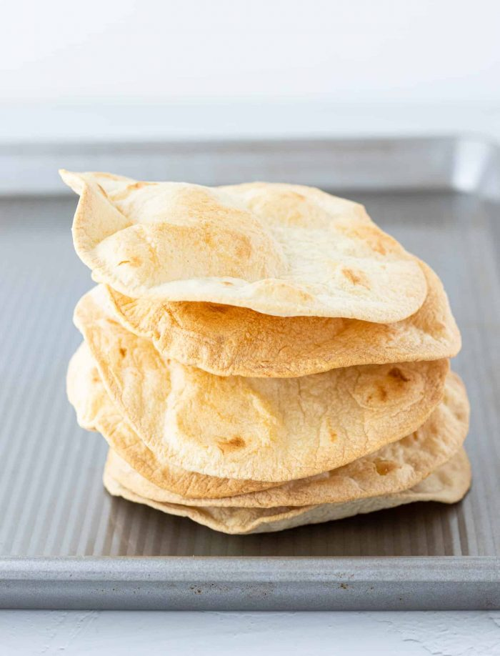 Crispy tortillas stacked on baking sheet
