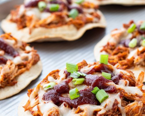 baked chicken tostadas on a baking sheet topped with BBQ sauce and green onion