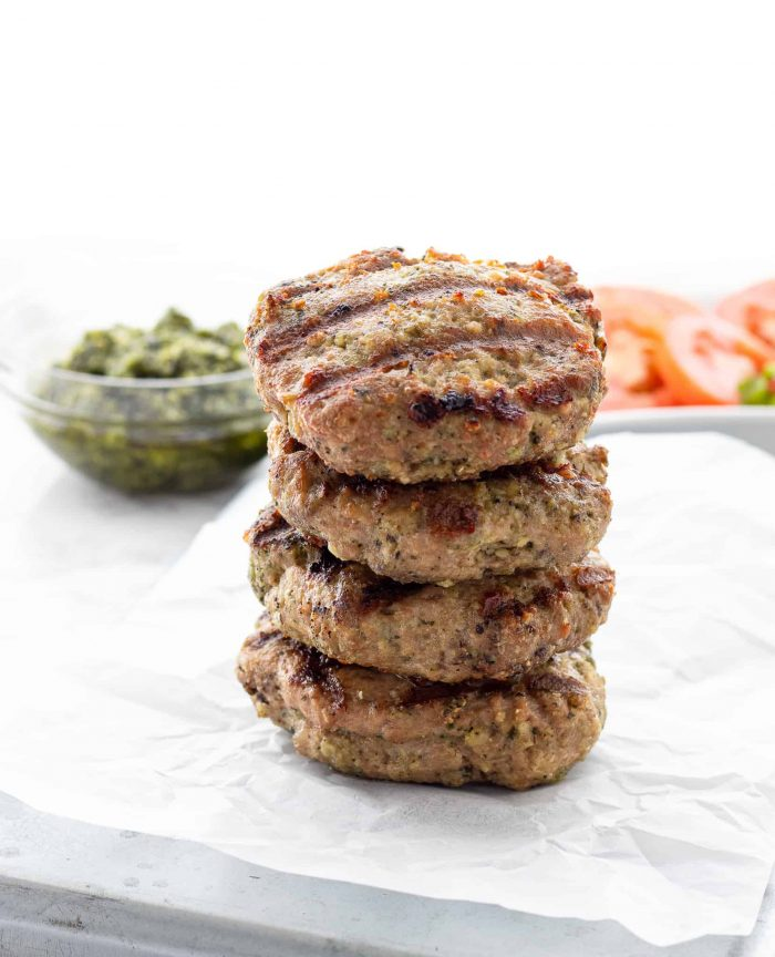 Four chicken pesto burgers stacked on top of each other.