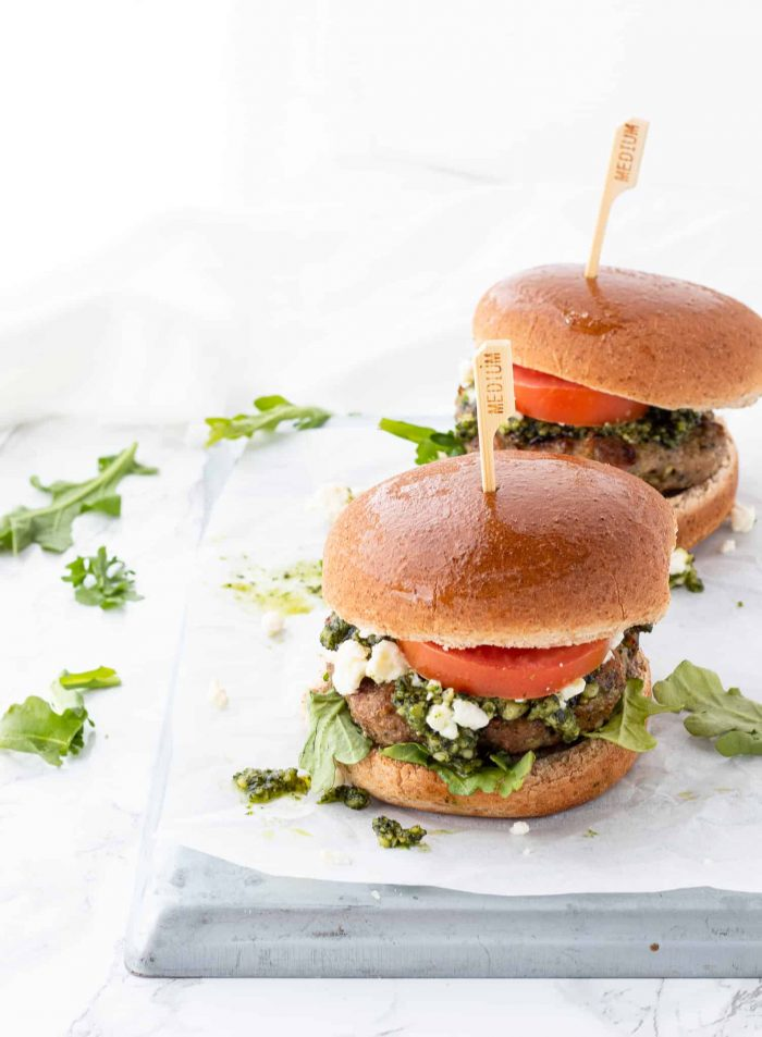 Two pesto chicken burgers served in buns