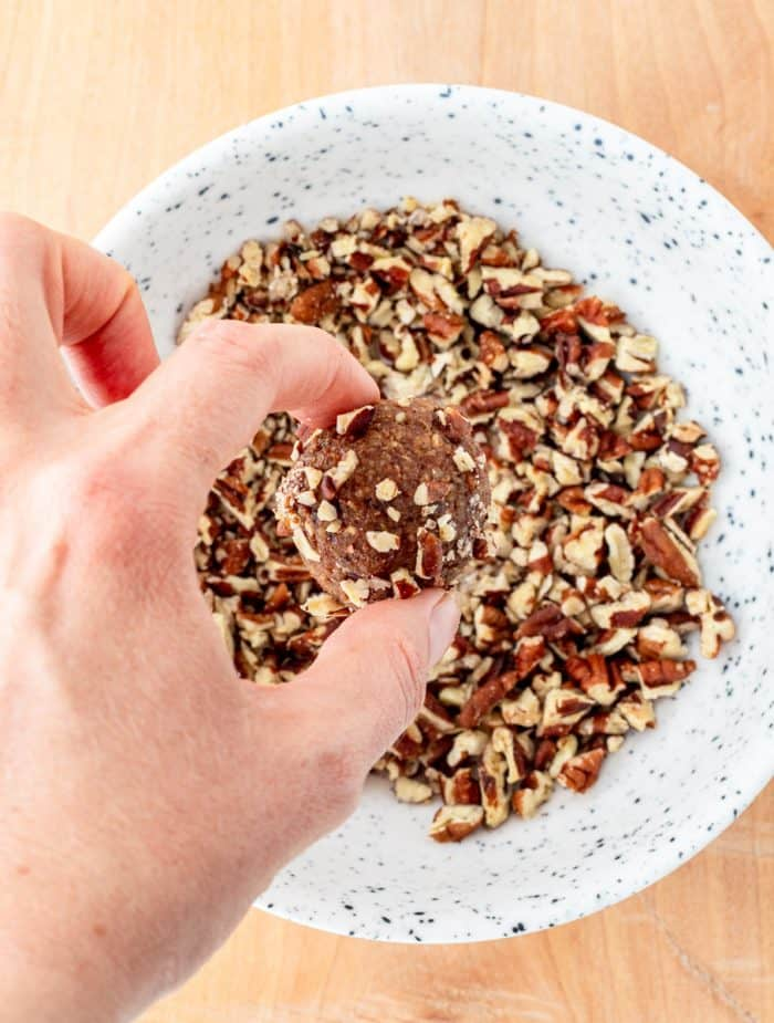 Rolling a pumpkin ball in chopped pecans