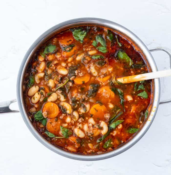 Overhead shot of a pot of Italian sausage soup with a spoon