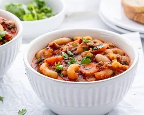 Italian sausage soup served in a white bowl
