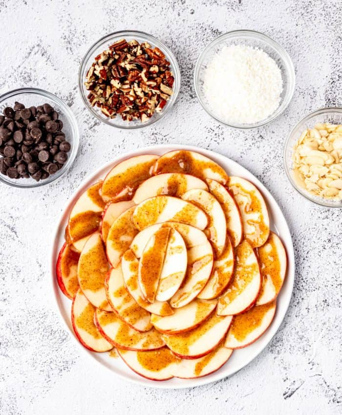 apple slices on a plate with caramel drizzle with toppings around it