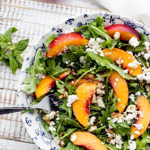 arugula nectarine salad topped with feta and chopped walnuts in a blue and white bowl with a fork