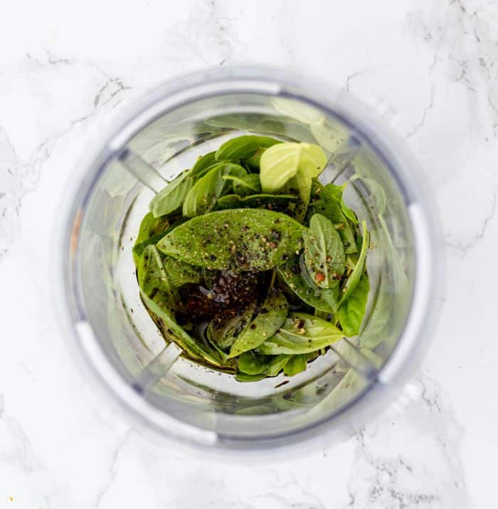 ingredients for basil dressing in a blender cup