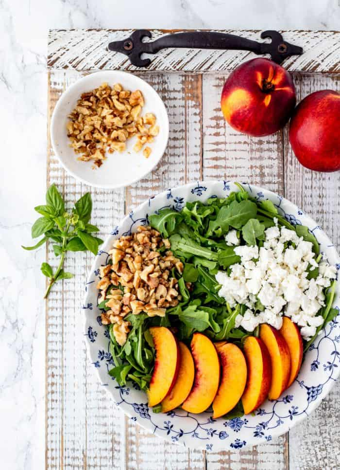 sliced nectarines, crumbled feta and chopped walnuts on a bed of arugula with nectarines. walnuts and fresh basil beside