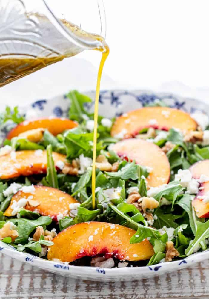 pouring basil dressing over nectarine salad in a blue and white bowl