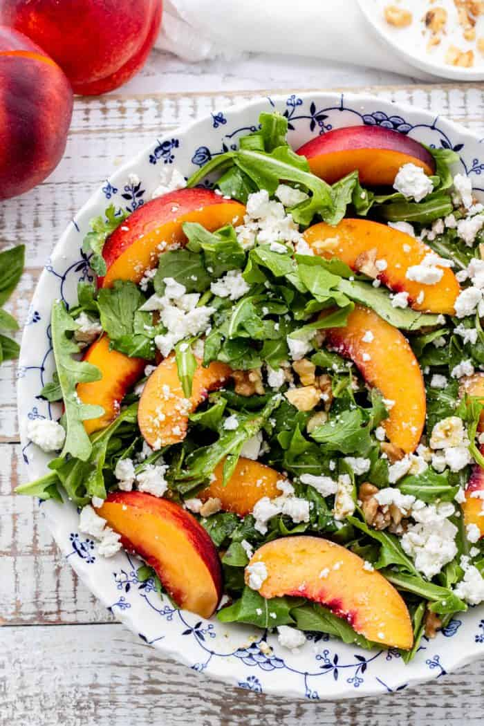 arugula nectarine salad topped with feta and chopped walnuts in a blue and white bowl