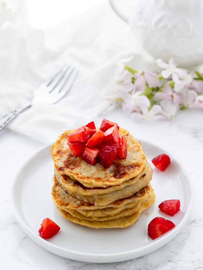 stack of pancakes topped with diced strawberries on white plate with fork and flowers in background