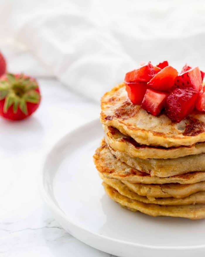stack of pancakes topped with diced strawberries with napkin and fresh strawberries in background