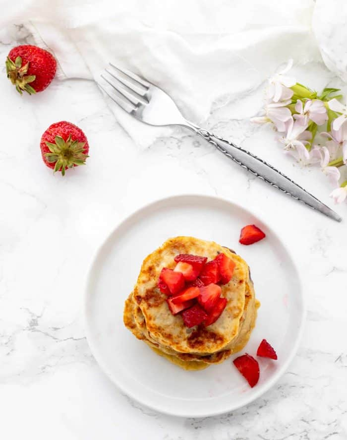 stack of mini pancakes topped with diced strawberries on a white plate surrounded by a fork and fresh strawberries