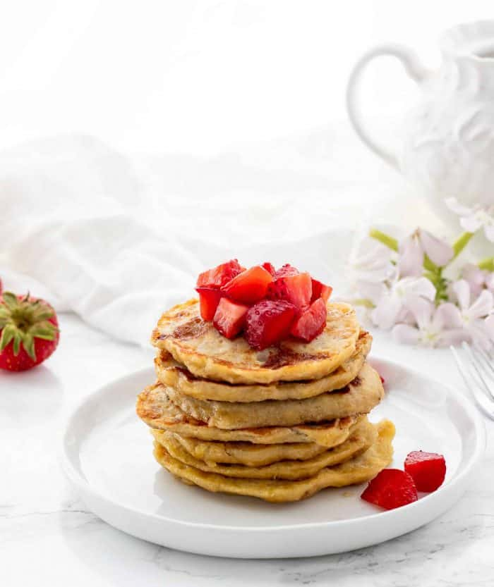 stack of pancakes topped with diced strawberries with strawberries and flowers in background