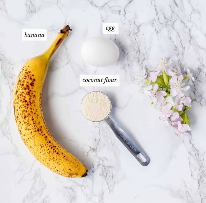 ingredients for banana egg pancakes with labels next to some pink flowers on a marble background