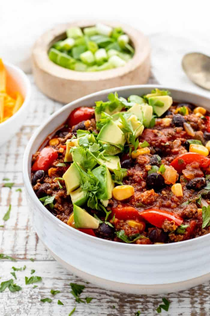 close up of bowl of beef and quinoa chili with diced avocado and cilantro
