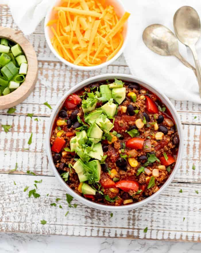 bowl of beef and quinoa chili with diced avocado and cilantro with cheese and diced green onion in bowls on the side