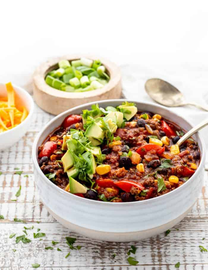 bowl of beef and quinoa chili with a spoon and diced avocado and cilantro