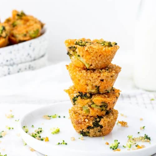 stack of broccoli cheddar cups on white plate with speckled bowl of quinoa cups in background