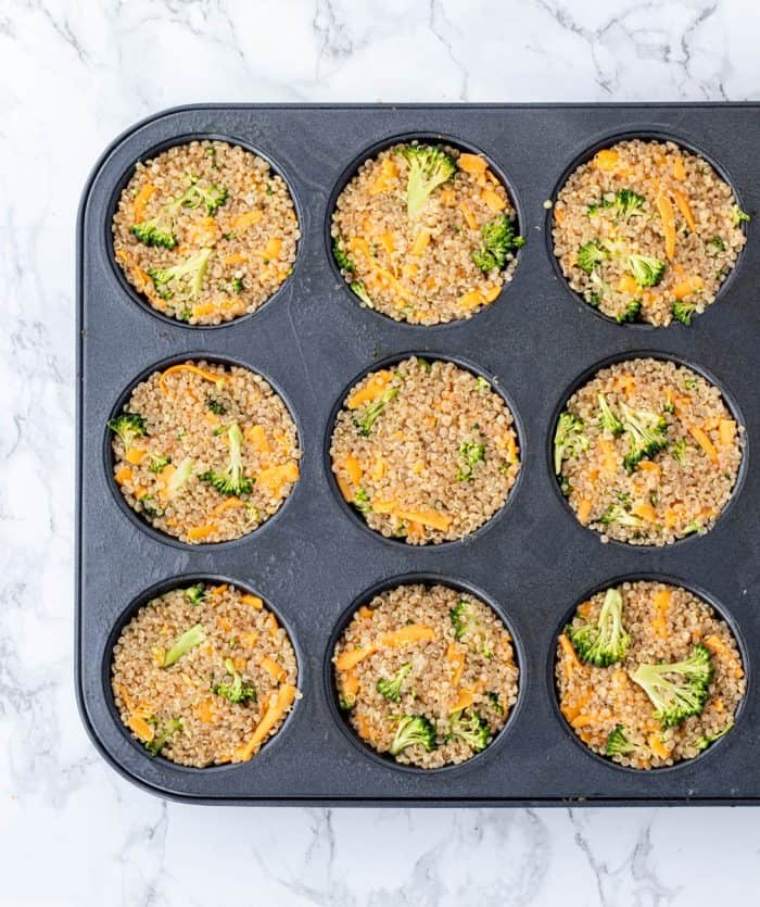 Broccoli cheddar muffins in a regular sized muffin tin on marble background