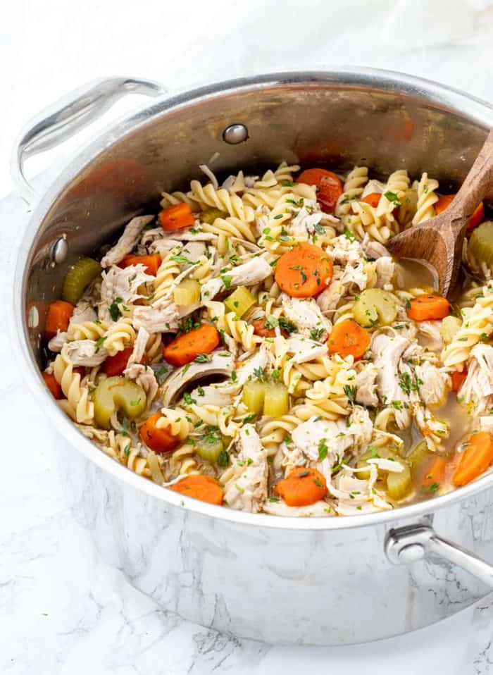large pot of chicken noodle soup with wooden spoon
