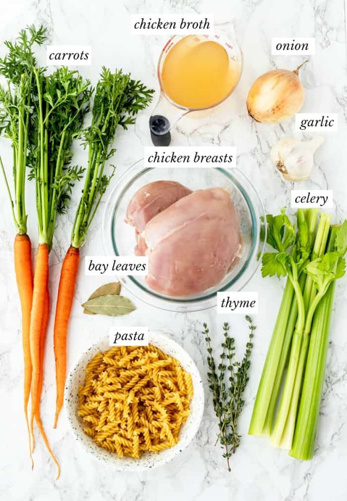 ingredients required to make chicken noodle soup with labels on a marble background