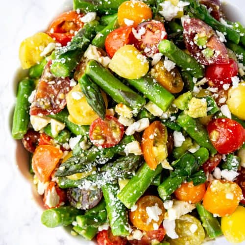 asparagus tomato salad with a sprinkle of feta cheese in a large bowl