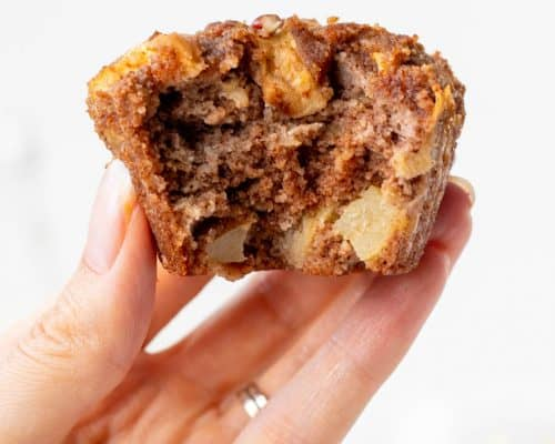 holding an apple muffin with a bite taken out of it