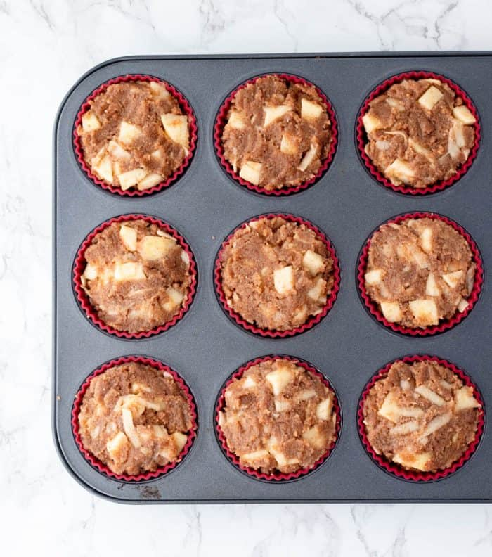 uncooked muffins batter in silicone muffin liners in muffin tin