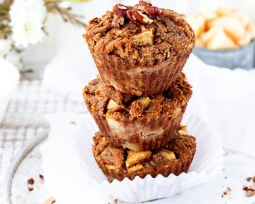 three apple muffins stacked with chopped pecans sprinkled around with apples and flowers in background